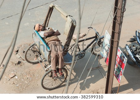 VARANASI, INDIA - DECEMBER 1: Unidentified Cycle rickshaw rests in awaiting a passenger on December 1, 2012 in Varanasi. Cycle rickshaws are widely used in cities of South, Southeast and East Asia. - stock photo