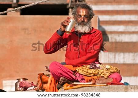 VARANASI, INDIA - FEBRUARY 19: A Hindu brahmin priest takes a break from prayer to drink water on the auspicious Maha Shivaratri festival on February 19, 2011 in Varanasi, Uttar Pradesh, India. - stock photo