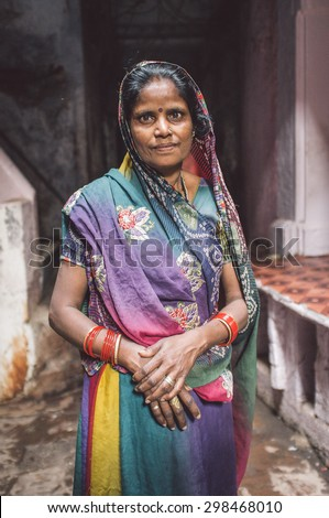 VARANASI, INDIA - 20 FEBRUARY 2015: Indian woman in colorful sari with bindi stands in street. Post-processed with grain, texture and colour effect. - stock photo