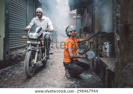 VARANASI, INDIA - 20 FEBRUARY 2015: Street vendor makes fire for milky tea in coal oven while motorcyclist passes by. Post-processed with grain, texture and colour effect. - stock photo