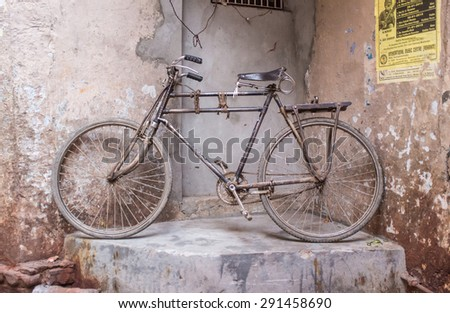 VARANASI, INDIA - 25 FEBRUARY 2015: Traditional Indian bicycle parked in corner of street. Bicycles are very common means of transportation on India's streets. - stock photo