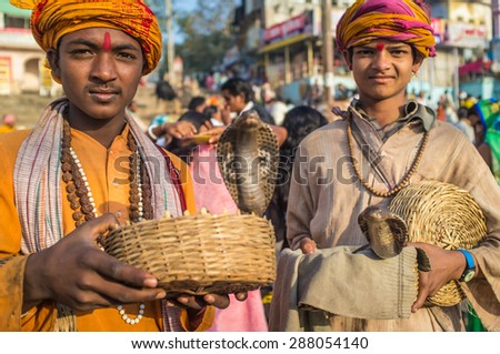 VARANASI, INDIA - 23 FEBRUARY 2015: Two Indian boys dressed up in religious clothes hold cobras in baskets. - stock photo