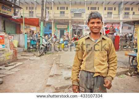 VARANASI, INDIA - JAN 4: Unidentified kid in dirty clothes standing on poor indian street with local stores and repair shops on January 4 2016. Varanasi urban agglomeration had population of 1,435,113 - stock photo