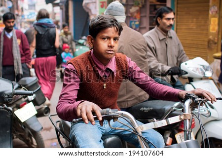 VARANASI, INDIA - JAN 4: Young man drive the old byke on the indian street with active movement of transport on January 4, 2013. Varanasi urban agglomeration had a population of 1,435,113 - stock photo