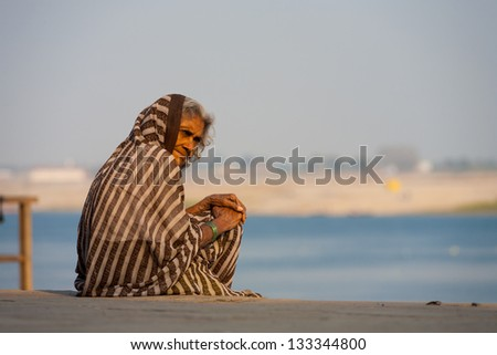VARANASI, INDIA - JANUARY 28, 2008: An unidentified Indian woman sits on a ghat outside her hospice on January 28, 2008 in Varanasi, India. The Ganges has several hospices for those soon to pass away - stock photo