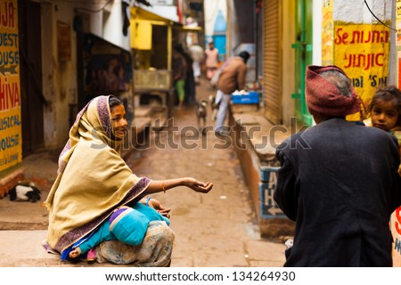 VARANASI, INDIA - JANUARY 31, 2008: An unidentified poor woman with baby begs for money from a passerby in the holy city of Varanasi, India on January 31, 2008. Poverty is a major issue in India - stock photo