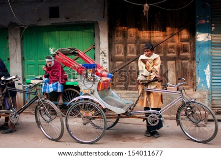 VARANASI, INDIA - JANUARY 4: Hard working rickshaw waits for the passengers with his vintage bicycle cab on the street on January 4, 2013. Varanasi urban agglomeration had a population of 1,435,113