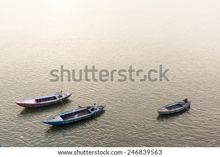 VARANASI, INDIA - JANUARY 05, 2015 : Three men rowing wooden boats on the Ganges river.