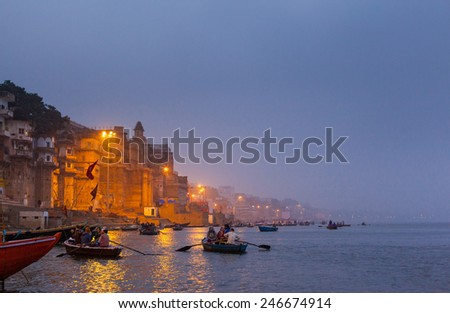 VARANASI, INDIA - JANUARY 05, 2015 : Tourist filled rowing boats on the Ganges just before dawn. Sunrise is a very popular time to view the Ghats and ancient buildings which line the river. - stock photo