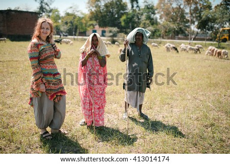 Varanasi, India - March 12 2015: Female tourist with local herds pose in the field not far from Varanasi - Mar, 12, 2015 at Varanasi, India