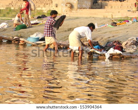 VARANASI, INDIA -  26 MARCH: Unidentified Indian Men, women and children wash clothes in Ganga river on March 26, 2006 in Varanasi, India.