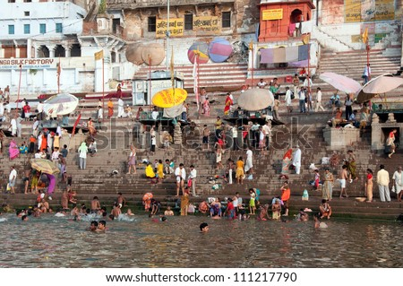 VARANASI, INDIA - MAY 15: An unidentified group of Indian people wash themselves in  river Ganga on MAY 15, 2012  in Varanasi, Central India. The holy ritual of washing is held every day. - stock photo