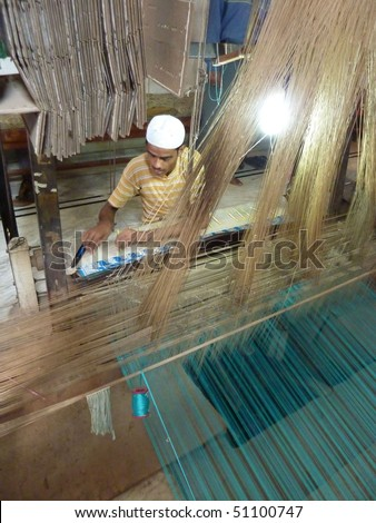 VARANASI, INDIA - NOV 6 -  Young muslim man runs a loom to weave silk brocade on Nov 6, 2009,  in Varanasi, India.