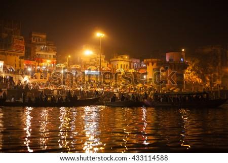 VARANASI, INDIA - NOVEMBER 25: Hindu people watching religious Ganga Aarti ritual (fire puja) from the water near Dashashwamedh Ghat on November 25, 2012 in Varanasi, Uttar Pradesh, Central India - stock photo