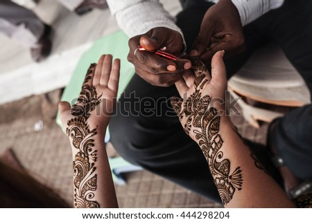 VARANASI , INDIA-  NOVEMBER 13, 2012: indian street  master uses  henna paste or mehndi application on white  tourist woman hand. Traditional Indian natural skin decoration, bio-tattoo - stock photo