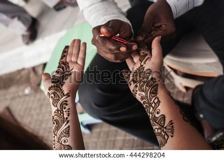 VARANASI , INDIA-  NOVEMBER 13, 2012: indian street  master uses  henna paste or mehndi application on white  tourist woman hand. Traditional Indian natural skin decoration, bio-tattoo - stock photo