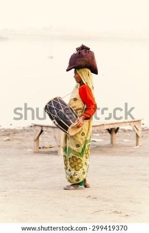 Varanasi, India - November 23, 2014: Indian villager woman in traditional dress sari walking and playing music at river side. - stock photo
