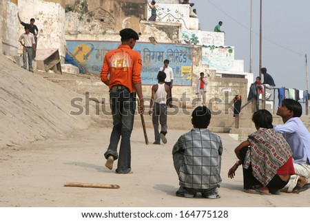 VARANASI, INDIA - NOVEMBER 27: Youth play cricket on ghat next to the Ganges River  in Varanasi, India, on November 27, 2008.  They aspire to escape poverty through professional sports. - stock photo