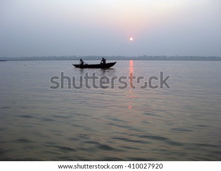 Varanasi, Uttar Pradesh, India - Boat with tourists in the Ganges River at dawn.