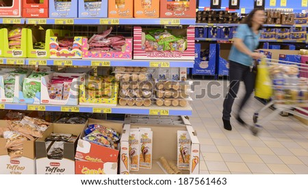 VARESE, ITALY-APRIL 11, 2014: Woman pushing a trolley in a supermarket aisle, in Varese.