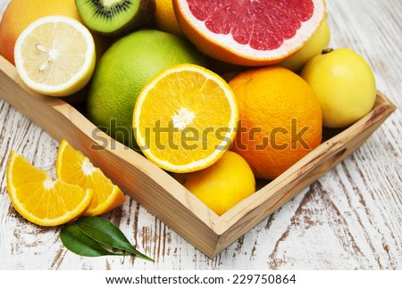 Variation of Citrus Fruits with leaves on the wooden box - stock photo