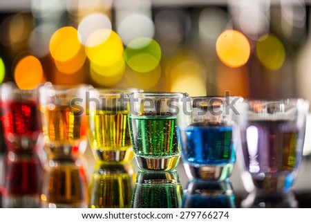 Variation of hard alcoholic shots served on bar counter. Blur bottles on background - stock photo