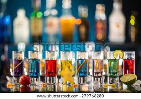 Variation of hard alcoholic shots served on bar counter. Blur bottles on background - stock photo