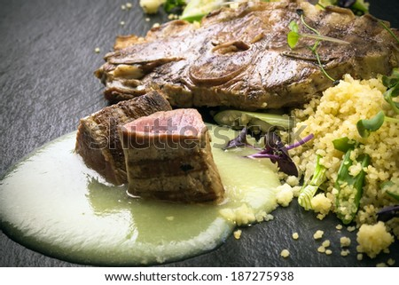 Variation of lamb filet and chop on asparagus cream with roasted couscous on spring onions   - stock photo