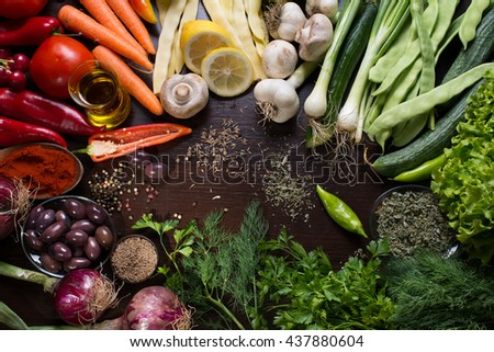 Variation of raw vegetables and spices on dark wooden background - stock photo