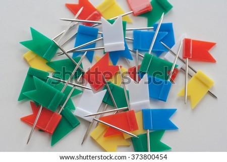 Varicolored plastic push pins looks like small flags - stock photo