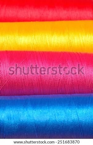 Varicolored spools thread macro background - stock photo