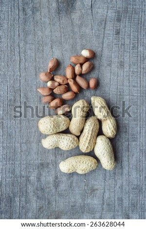 varied selection nuts, walnuts, almonds, peanuts, peeled, peanuts in the shell on a wooden table - stock photo