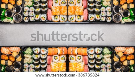 Varied Sushi sets assortment in bento boxes on gray stone background, top view, horizontal border or banner.  Japanese and Asian food. - stock photo