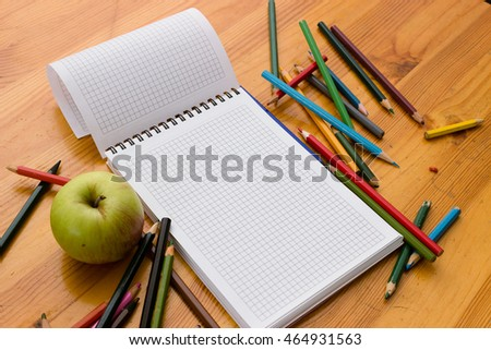 Variegated colored pencils, white square-lined paper notebook and green apple on a light orange wooden study table