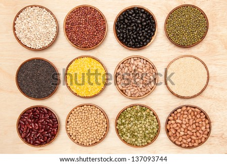 Varieties of beans, peas and sesame in wooden bowls on  background. - stock photo