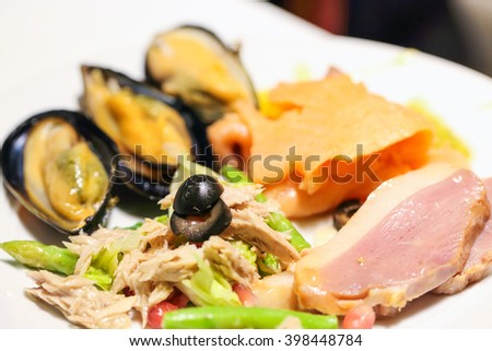 Variety appetizer salad with duck slice oyster tuna on a plate  - stock photo