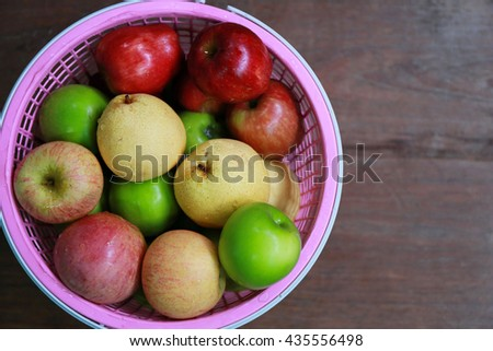 variety apple in basket on wood plank ,fresh apple in plastic basket after harvest from garden - stock photo
