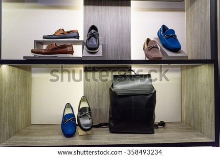 Variety colorful leather casual derby, slip-ons (or drivers) shoes and business handbag on the shelf in the menâ??s fashion footwear and accessories shop. Business and executive, self-grooming concept. - stock photo