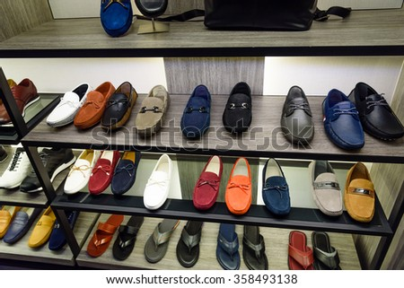 Variety colorful slip-ons or drivers shoes and sandals on the shelf in the menâ??s fashion footwear and accessories shop in Singapore. Casual, fashion and work shoes for men. - stock photo