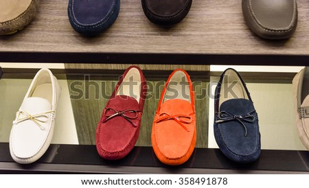 Variety colorful slip-ons or drivers shoes on the shelf in the menâ??s fashion footwear and accessories shop in Singapore. Casual, fashion and work shoes for men. - stock photo