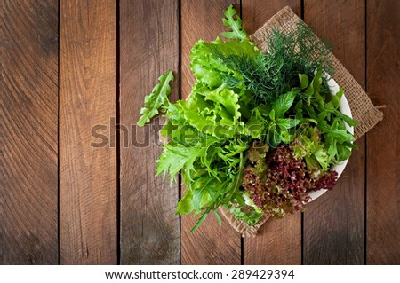 Variety fresh organic herbs (lettuce, arugula, dill, mint, red lettuce) on wooden background in rustic style. Top view - stock photo