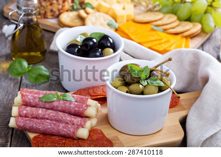 Variety of appetizers on dinner table salami, cheese, olives, capers, pepperoni - stock photo