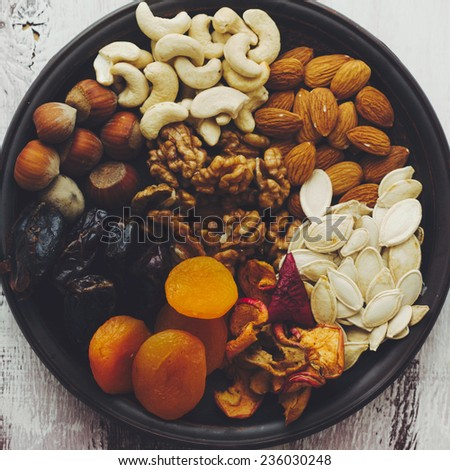 Variety of 8 assorted nuts and dried fruits, top view - stock photo