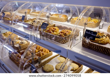 Variety of baked products in baskets with bread name and price on black small sign board at a bakery shop - stock photo
