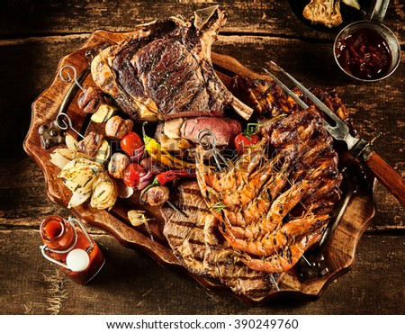Variety of barbecue beef, shrimp and various vegetables served on table with oil, ketchup and seasonings - stock photo