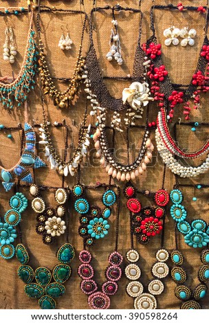 Variety of Beautiful Shine Color Stone Plastic Jewellery Necklaces Hanging on The Wall for Sale in The Market - stock photo