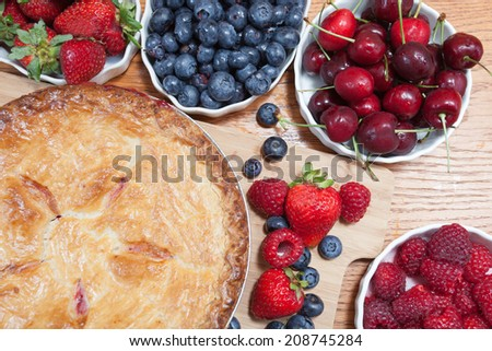 Variety of berries garnish a golden delicious freshly baked country-style dessert berry pie. - stock photo