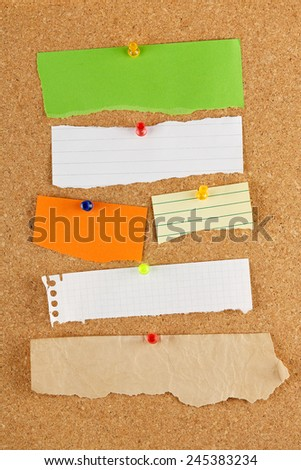 variety of blank torn notes on cork notice board - stock photo
