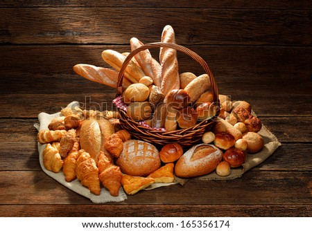 Variety of bread in wicker basket on old wooden background. - stock photo