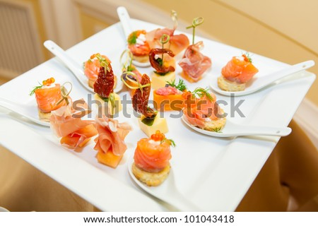 variety of canapes on a plate - stock photo